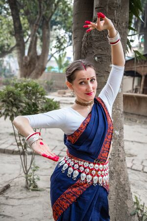 portrait of beautiful young Caucasian classical odissi dancer wears traditional costume and posing Odissi dance mudra in the rainforest. Stock Photo