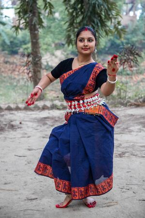 portrait of beautiful young Indian classical odissi dancer wears traditional costume and posing Odissi dance mudra in the rainforest.