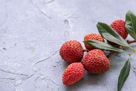 Lychee with leaves on gray background. Tropical fruit.