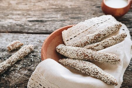 freshly baked fresh homemade breadsticks with sesame on clay plate with milk on a wooden table. Country food. Rustic style. top view, copy space