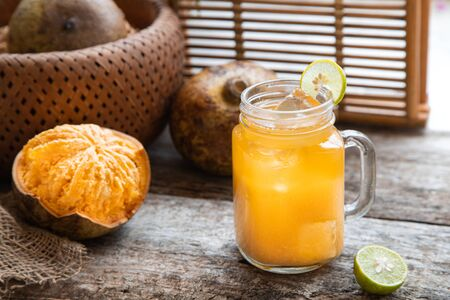 exotic fruit juice from Bel fruit or wooden Apple called in India Bel Ka Sharbat. cold fruit drink with ice and Bel fruit slices on wooden rustic background. natural detox. vitamins for immunity. Stock fotó