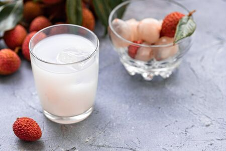 Sweet lychee juice on the gray background Closeup of fresh lychee juice with fruits Stock Photo