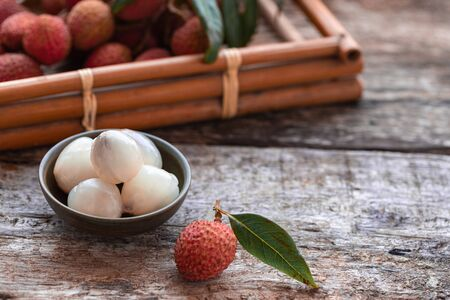 Lychee with leaves on gray background. Tropical fruit