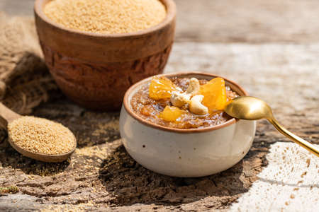 Delicious amaranth topped with cashew nuts. Healthy colorful gluten free food concept. Raw Organic Amaranth Grain in a Bowl witn wooden spoon. Rustic wooden background. healthy vegetarian Breakfast