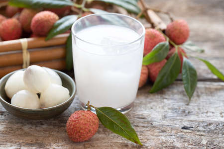 Sweet lychee juice on the wooden rustic background Closeup of fresh lychee juice with fruits Stock Photo