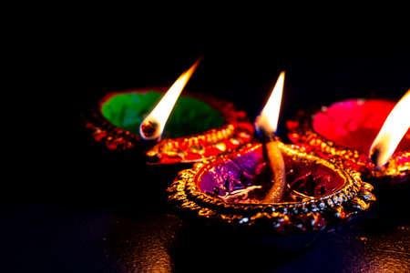 burning decorated ceramic oil lamp diya, on Happy Diwali, Shubh Diwali with beautiful dark blue background, copy space Stock Photo
