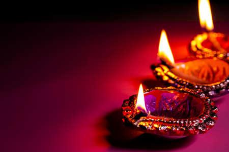 burning diya on Happy Diwali purple background for light festival of India, copy space
