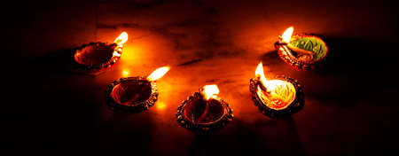 burning decorated ceramic oil lamp diya, on Happy Diwali, Shubh Diwali
