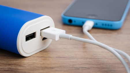 power equipment: Charging a smartphone from powerbank on wooden table