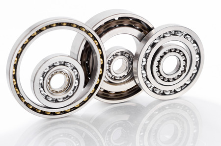 bearings: Ball bearings on reflected surface and white background