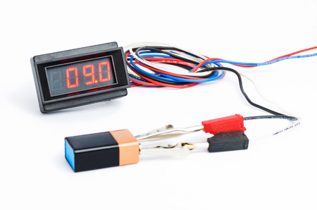 manual test equipment: Testing battery with digital voltmeter illustration isolated on white