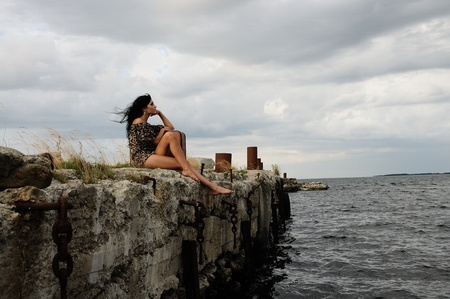 windswept: A beautiful brunette woman in mini dress and bare feet sits alone on a windswept stone wall bordering the sea Stock Photo