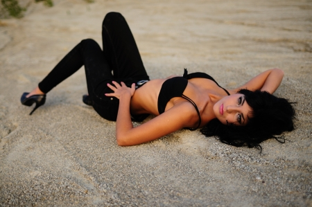 sexy babe: Hot Sexy Babe In Black, Gorgeous sexy brunette woman dressed in black bikini and tights lying on her back in sand looking across at camera. Stock Photo