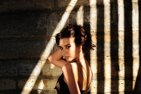 contrasty: Seductive brunette woman looking back over her shoulder while standing in dramatic striped contrasty shadows Stock Photo