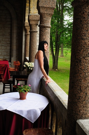 treed: Beautiful woman standing under arched stone columns looking out over treed green grounds.