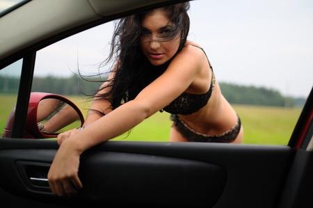 Woman In Bikini At Open Car Window leaning in towards the camera. Stock Photo - 12037116