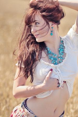 zerzaust: Carefree Country Girl. Eine sorglose zerzausten Rotschopf M�dchen vom Land stellt in einem Weizenfeld, close-up Portr�t