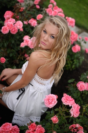 strapless: Blond woman in strapless white dress seated amongst the roses.
