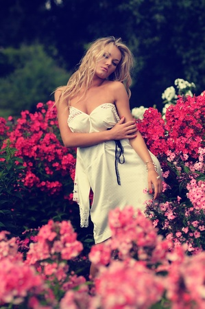 strapless: Low angle portrait of a sexy blonde woman posing in a strapless white dress amongst colourful bushes of pink flowers.