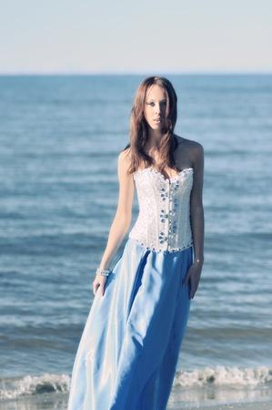donna in abito lungo sul lato mare.