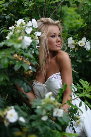 Beautiful blonde woman wearing an off the shoulder white summer dress posing amongst white flowers and foliage photo