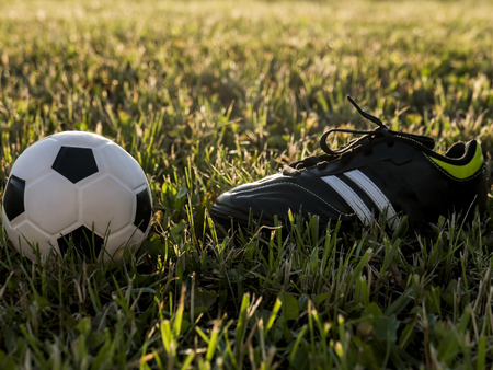 soccer shoes: Soccer shoes and football on the green grass. Outdoor. Sunset. Football or soccer concept Stock Photo