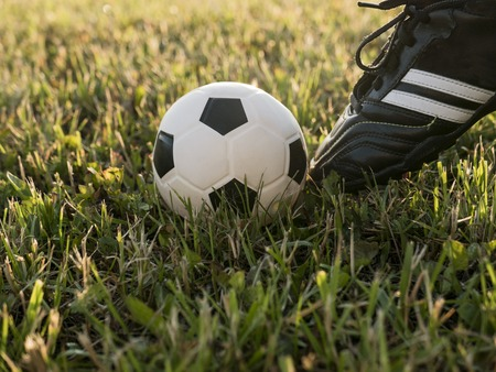 soccer shoes: Soccer shoes and football on the green grass. Football or soccer concept