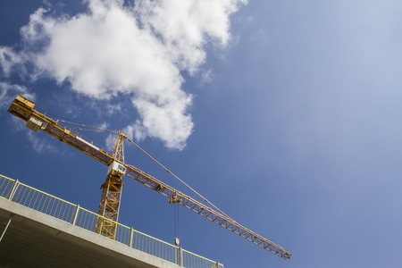 constitutive: Construction site. New building. Yellow construction tower crane against blue sky with clouds. Stock Photo