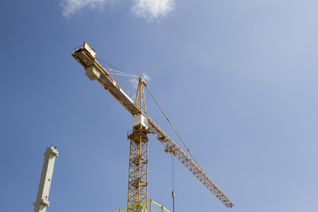 constitutive: Part of yellow construction tower crane against blue sky Stock Photo