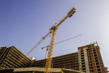 Construction site. New building. Yellow construction tower crane against blue sky. Construction concept.