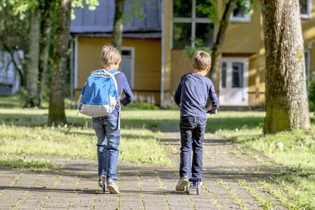 Jongetje rijden met scooter buiten. Vrijetijdsbesteding Stockfoto