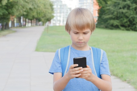 Boy with mobile phone in the street. Child looks at the screen, use apps, plays, writes or reads message. City background. Childhood, school, technology, leisure concept 免版税图像