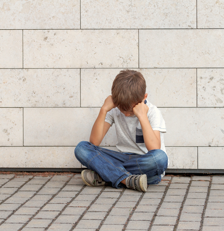 sitting on the ground: Sad, lonely, unhappy, disappointed, upsed, tired child sitting alone on the ground Outdoor Stock Photo