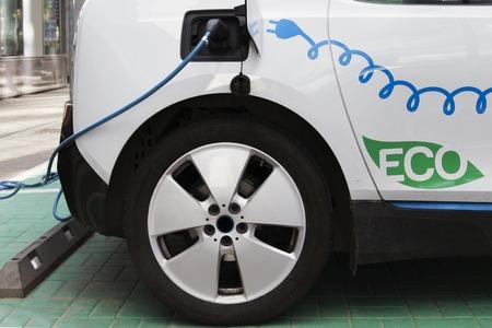 駅を充電する電気自動車。電気自動車充電中に差し込まれている電源のクローズ アップ。 写真素材
