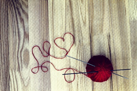 wool ball: Knitting hobby concept. Red wool ball and heart shaped thread on wooden background. Toned image