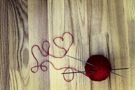 wool ball: Knitting hobby concept. Wool ball and heart shaped thread on wooden background. Toned image