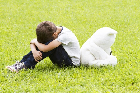 Sad disappointed little boy sitting with a teddy bear. Both turned away. Both lowered their heads. Outdoor. Sadness, fear, frustration, loneliness concept Stock Photo