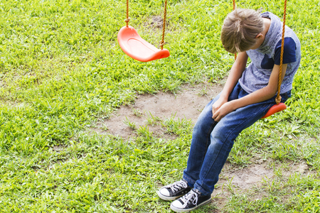 屋外の遊び場のブランコに座っている悲しい孤独な少年。悲しい、孤独、抑うつ、不幸な気分