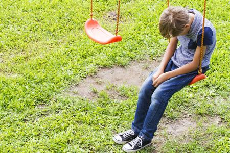trieste eenzame jongen zit op schommeling in de speeltuin buiten. Verdrietig, eenzaam, depressief, ongelukkig stemming