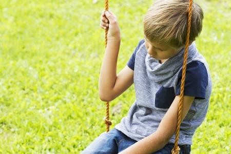 屋外の遊び場のブランコに座っている悲しい孤独な少年。クローズ アップ。悲しい、孤独、抑うつ、不幸な気分