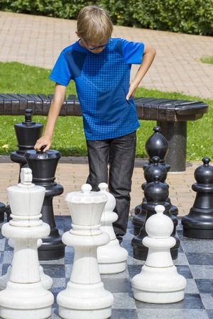 strategically: Boy playing giant chess outdoor. Child thinking strategically about his next move Stock Photo