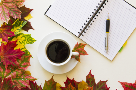 Open notebook with empty space for text, pen and cup of coffee, framed with autumn leaves. White background. Flat lay. Top view