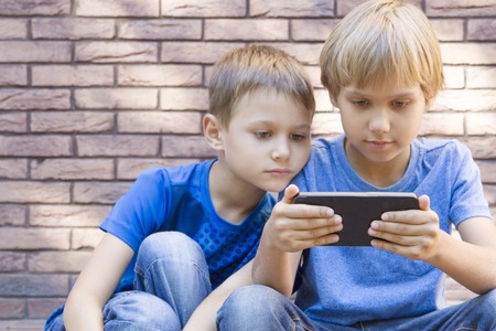 Children with mobile phone. Boys smiling, looking to phone, playing games or using application. Outdoor. Technology education leisure friendship people concept Stockfoto