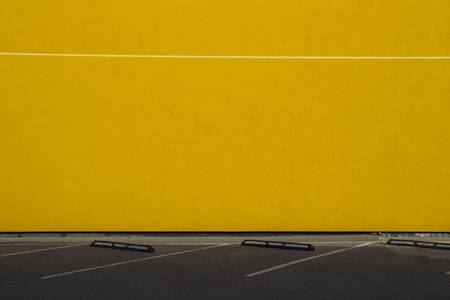 Yellow wall as background in outdoor parking lot Stock Photo