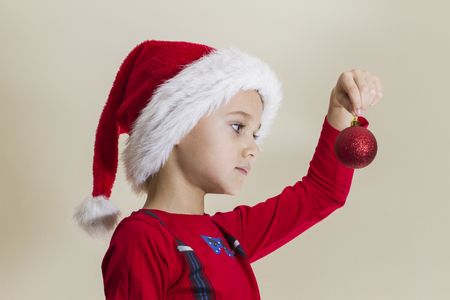 Small child in Santa cap looking at Christmas toy at home
