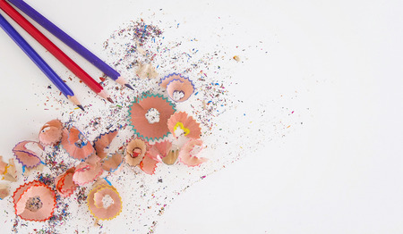Multicolored pencils and shavings on white background with copy space. Top view
