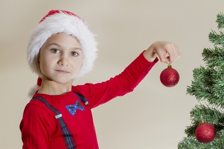Little kid in Santa cap with Xmas toy while decorating Christmas tree at home