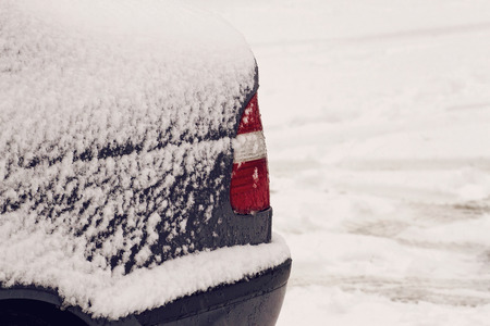 snowscene: Back of a car covered with snow after snowfall in winter. Close up Stock Photo