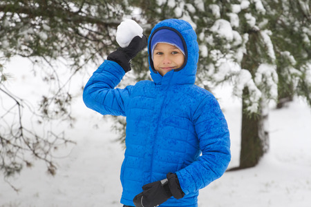 Boy throw snowball. Wintertime fun game outdoor 免版税图像