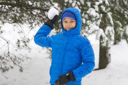 Jongen gooien sneeuwbal. Wintertijd leuk spel outdoor